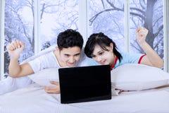 Koppla ihop med bärbara datorn på säng i vinterdag Arkivfoton