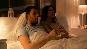 Koppla ihop med hållande ögonen på tv för popcorn på natten hemma stock video