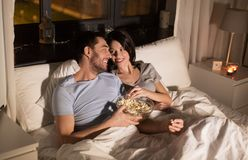 Koppla ihop med hållande ögonen på tv för popcorn på natten hemma Royaltyfri Bild