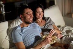 Koppla ihop med hållande ögonen på tv för popcorn på natten hemma royaltyfri fotografi