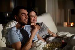 Koppla ihop med h?llande ?gonen p? tv f?r popcorn p? natten hemma royaltyfri fotografi