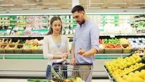 Koppla ihop med mat i shoppingvagn på livsmedelsbutiken arkivfilmer