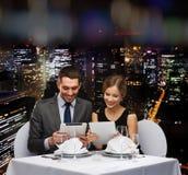 Koppla ihop med menyer på minnestavlaPC på restaurangen Royaltyfri Fotografi