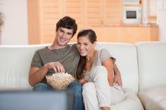 Koppla ihop med popcorn på sofaen som håller ögonen på en film Royaltyfria Bilder