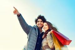 Koppla ihop med shoppingpåsar som pekar in i avstånd royaltyfri foto