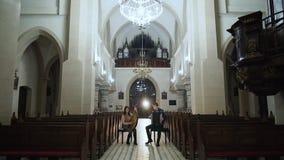 Koppla ihop musiker spelar bandura och dragspelet i katolsk kyrka lager videofilmer