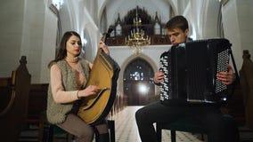 Koppla ihop musiker spelar bandura och dragspelet i katolsk kyrka stock video
