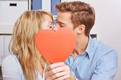 Koppla ihop nederlag bak röd hjärta för en kyss Royaltyfri Fotografi