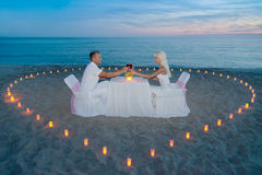 Koppla ihop på den romantiska matställen för stranden med stearinljushjärta Arkivbilder