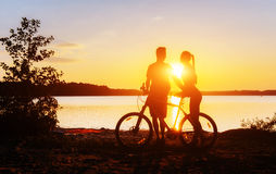 Koppla ihop på en cykel på solnedgången vid sjön Arkivfoton