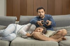 Koppla ihop på en soffa, man spelar videospel, medan kvinnan är takien royaltyfri foto