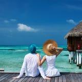 Koppla ihop på en strandbrygga på Maldiverna Arkivfoto