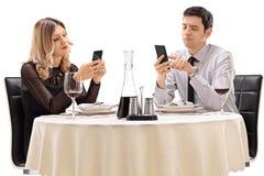 Koppla ihop på ett datum som spelar med deras telefoner Arkivbilder