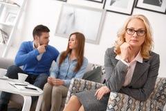 Koppla ihop på fastighetförsäljningskontoret med medlet som ser den allvarliga kameran royaltyfri bild
