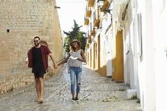 Koppla ihop på ferie som går i Ibiza gator med en resehandbok royaltyfria bilder