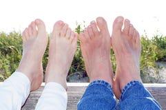 Koppla ihop på stranden med fot i sommarsolljuset Royaltyfri Bild