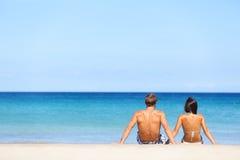 Koppla ihop på strandsammanträde i sand som ser havet Arkivfoto