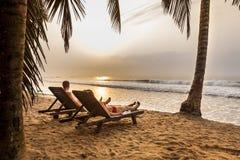 Koppla ihop på sunbedsna på den tropiska stranden Arkivfoto
