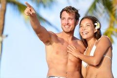 Koppla ihop på stranden som är lycklig i swimwear, att peka för man Royaltyfri Foto