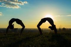 Koppla ihop praktiserande yoga i parkera på solnedgångdroppe tillbaka Royaltyfria Foton
