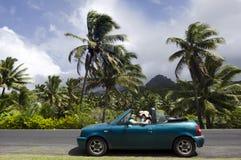 Koppla ihop resanden med den konvertibla bilen i en Stillahavs- ö Arkivfoton