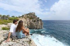 Koppla ihop sammanträde i ett hållande ögonen på havlandskap för klippan Royaltyfria Foton