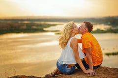 Koppla ihop sammanträde på banken av floden på solnedgången kyss Royaltyfria Bilder