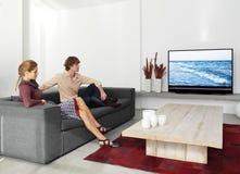 Koppla ihop sammanträde på den hållande ögonen på tvllen för soffan Arkivfoto