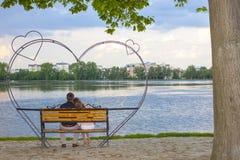 Koppla ihop sammanträde på en bänk framme av en stor sjö Arkivfoto