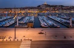 Koppla ihop sammanträde på en bänk i Vieux port i Marseille Arkivbild