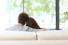 Koppla ihop sammanträde på en soffa som ser till och med fönster royaltyfria bilder