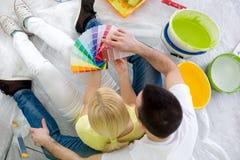 Koppla ihop sammanträde på golvet omgiven utrustning för att måla royaltyfri foto