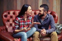Koppla ihop sammanträde på soffan och ha en trevlig konversation arkivfoto