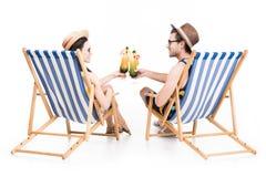 koppla ihop sammanträde på strandstolar och att klirra med coctailexponeringsglas, royaltyfri fotografi