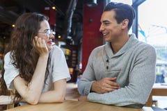 Koppla ihop sammanträde på tabellen och samtal i coffee shop arkivfoton