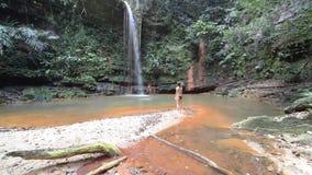 Koppla ihop simning in i mångfärgad naturlig pöl med den sceniska vattenfallet i rainforesten av Lambir kullar nationalparken, Bo lager videofilmer