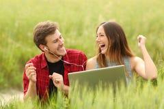 Koppla ihop sjunga och lyssnande musik från en bärbar dator royaltyfri fotografi
