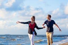Koppla ihop spring till och med sand och vågor på stranden Arkivfoton