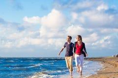 Koppla ihop spring till och med sand och vågor på stranden Royaltyfria Foton
