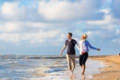 Koppla ihop spring till och med sand och vågor på stranden Arkivbild