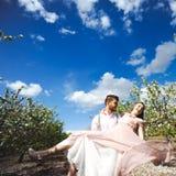 Koppla ihop ståenden av en flicka och en grabb som söker efter en bröllopsklänning, ett rosa klänningflyg med en krans av blommor Royaltyfria Foton