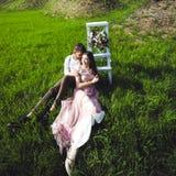 Koppla ihop ståenden av en flicka och en grabb som söker efter en bröllopsklänning, ett rosa klänningflyg med en krans av blommor Royaltyfri Bild