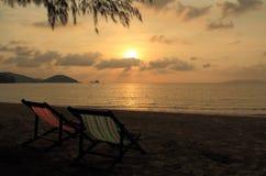 Koppla ihop stol på stranden på solnedgångtid Royaltyfria Bilder