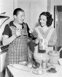 Koppla ihop tillsammans i köket som bakar en kaka (alla visade personer inte är längre uppehälle, och inget gods finns Leverantör Arkivfoton