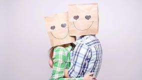Koppla ihop tillsammans mannen och kvinnan med påsar över huvud på grå bakgrund stock video