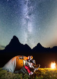 Koppla ihop vänner som ser till den stjärnklara himlen för sken och den mjölkaktiga vägen nära belysningtältet i campa på natten  Arkivfoto