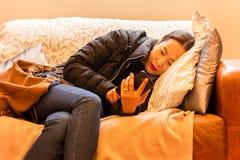 Kopplad av härlig kvinna genom att använda den smarta telefonen som ligger på en soffa i vardagsrummet royaltyfri fotografi