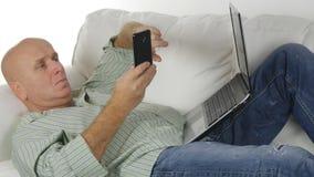 Kopplad av man som vilar i soffatexten genom att använda Smartphone royaltyfria bilder