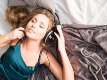 Kopplad av ung kvinna, medan lyssna till musikspelaren till och med hörlurar i bekväm säng Royaltyfri Bild