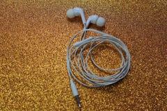 Kopplad från guld- bakgrund för vit headphone royaltyfria foton